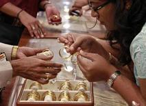 Покупательница выбирает золотые украшения в магазине в Коччи 19 апреля 2013 года. Цены на золото стабильны по мере отступления доллара от минимума шести недель на фоне улучшения экономических показателей США. REUTERS/Sivaram V