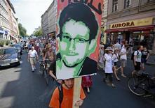 Демонстрант несет портрет американского беглеца Эдварда Сноудена на манифестации в Берлине 27 июля 2013 года. Сноуден покинул аэропорт Шереметьево, где провел более месяца в транзитной зоне, прося убежища, сообщил в пятницу представитель аэропорта. REUTERS/Pawel Kopczynski