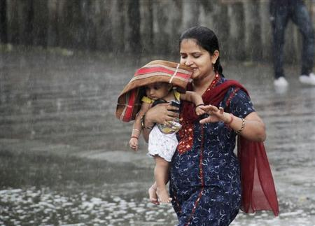 A woman carries her child through a heavy rain shower in the northern Indian city of Chandigarh June 11, 2013. REUTERS/Ajay Verma/Files