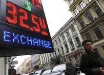 Женщина проходит мимо пункта обмена валюты в Санкт-Петербурге 3 октября 2011 года. Рубль торгуется с незначительной негативной динамикой утром пятницы, сместившись в область повышенных интервенций Центробанка - локальный спрос на валюту и дорогой доллар на форексе компенсируют текущий положительный настрой инвесторов к риску и сырью после сильной американской статистики. REUTERS/Alexander Demianchuk