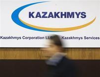 Человек проходит мимо вывески Казахмыса в офисе компании в Алма-Ате 15 мая 2013 года. Один из крупнейших акционеров ENRC - медная корпорация Казахмыс приняла предложение о продаже своих акций горнорудного гиганта, сообщила компания в пятницу. REUTERS/Shamil Zhumatov