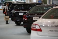 Visitante examina carros da Toyota no showroom da companhia, em Tóquio. A Toyota Motor elevou sua estimativa para lucro operacional para o ano financeiro com encerramento em março de 2014 em 7,8 por cento à medida que a desvalorização do iene torna as exportações mais lucrativas e registra vendas mais fortes nos Estados Unidos. 1/08/2013. REUTERS/Issei Kato