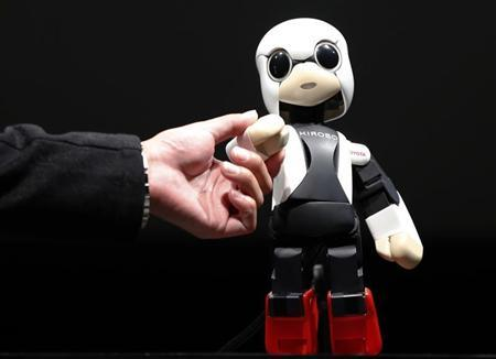 Humanoid communication robot Kirobo shakes hands with Tomotaka Takahashi, CEO of Robo Garage Co and project associate professor, research centre for advanced science and technology, the University of Tokyo, during its unveiling in Tokyo June 26, 2013. REUTERS/Toru Hanai