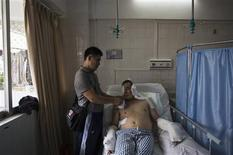 Li Jianhuang (L) feeds his brother, blogger and online whistleblower Li Jianxin, who is waiting for a fourth operation at a hospital in the southern Chinese city of Huizhou, Guangdong province July 23, 2013. REUTERS/Tyrone Siu