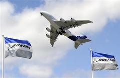 Boeing flags flutter as an Airbus A380, the world's largest jetliner, takes part in a flying display during the 49th Paris Air Show at the Le Bourget airport near Paris June 25, 2011. REUTERS/Gonzalo Fuentes