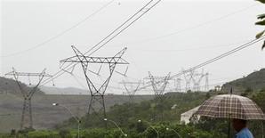 Residente local anda próximo a torres de transmissão de energia perto da hidrelétrica de Furnas, em Minas Gerais. A carga de energia elétrica no Sistema Interligado Nacional (SIN) em julho cresceu nas comparações anual e mensal informou nesta segunda-feira o Operador Nacional do Sistema (ONS), afirmando que o setor industrial do Sudeste ainda está sem mostrar recuperação definida. 14/01/2013. REUTERS/Paulo Whitaker