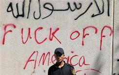 Сотрудник полиции охраняет посольство США в Каире, стена которого исписана граффити, 12 сентября 2012 года. Посольства Соединенных Штатов на Ближнем Востоке и в Африке останутся закрытыми еще неделю в связи с угрозой акций насилия со стороны исламистов, считающейся самой высокой за последние годы. REUTERS/Mohamed Abd El Ghany