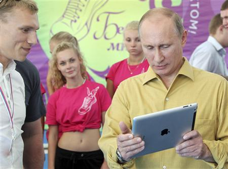 Russian President Vladimir Putin (R) holds an iPad as he talks to participants of a forum of pro-Kremlin youth groups at Lake Seliger, some 400km (248 miles) north of Moscow, August 2, 2013. REUTERS/Michael Klimentyev/RIA Novosti/Kremlin