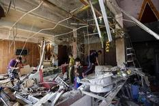 Youths survey and take pictures of the debris after a suicide bomb attack at a cafe the night before, in Baghdad June 17, 2013. REUTERS/Saad Shalash