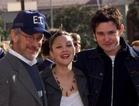 """Director Steven Spielberg and cast members Drew Barrymore and Henry Thomas (R) pose together as they arrive for the premiere of the 20th anniversary verison of their film """"E.T. The Extra Terrestrial"""" March 16, 2002 in Los Angeles file photo. REUTERS/Rose Prouser RMP - RTR2MFM"""