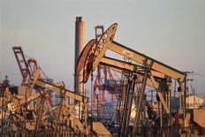Станки-качалки на Уилмингтонском нефтяном месторождении около Лонг-Бич в Калифорнии 30 июля 2013 года. Цены на нефть снижаются вместе с опасениями за поставки из ряда стран, но поддержку рынку дает прогноз, что запасы нефти в США снизились на прошлой неделе. REUTERS/David McNew