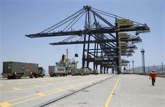 A worker walks past trucks as they line up to load containers onto a ship at a port in Ningbo, Zhejiang province in this July 9, 2013 file photograph. REUTERS/William Hong/Files