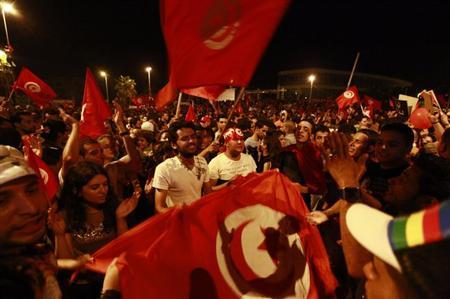 Anti-government protesters wave national flags during a demonstration in Tunis August 6, 2013. REUTERS/Anis Mili