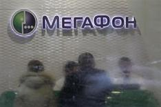 Customers and staff are seen through the partially cleaned window of a Megafon shop in Moscow November 28, 2012. REUTERS/Sergei Karpukhin