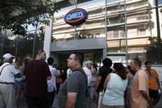 People wait outside a Greek Manpower Employment Organisation (OAED) office at Kalithea suburb in Athens August 8, 2013. REUTERS/Yorgos Karahalis