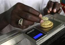 El precio del oro subió el jueves casi un 2 por ciento a 1.310 dólares la onza, gracias a una recuperación inesperadamente sólida de las importaciones y exportaciones chinas que generó optimismo sobre la economía, impulsando el atractivo del metal como cobertura contra la inflación. En la foto de archivo, un empleado de una minera en Sudán pesa tres piezas de oro. Jul 30, 2013. REUTERS/Mohamed Nureldin Abdallah
