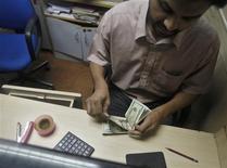 El dólar cayó contra las principales divisas el jueves por quinta sesión consecutiva, debido a que recientes datos económicos y comentarios de funcionarios de la Reserva Federal generaron incertidumbre sobre cuándo el banco central de Estados Unidos comenzará a reducir su programa de estímulo. En la foto de archivo, un empleando de un banco en India cuenta un fajo de dólares. Julio 23, 2013. REUTERS/Anindito Mukherjee