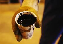 Рабочий держит стакан с сырой нефтью, добытой компанией Cenovus на нефтяных песках в канадской провинции Альберта, 9 июля 2012 года. Бум сланцевой нефти в Северной Америке удерживает мировые цены на нефть от резкого роста, в то время как несколько участников ОПЕК испытывают трудности в добыче, говорится в ежемесячном докладе Международного энергетического агентства (IEA). REUTERS/Todd Korol