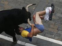 A runner gets gored by a bull on Estafeta street during the sixth running of the bulls of the San Fermin festival in Pamplona, Spain, in this July 12, 2013 file photo. Far from the narrow cobblestoned streets of Pamplona, a drag-racing strip could be an unlikely field of dreams for Americans who yearn to run with the bulls, Spanish style. The fenced-in quarter-mile (400-meter) strip of asphalt outside Richmond, Virginia will be the launching pad, August 24, 2013, for the Great Bull Run, which organizers say will be the first circuit of bull-running events across the United States. REUTERS/Susana Vera/Files