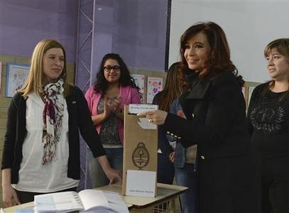 Argentine President Cristina Fernandez (R) casts her vote at a polling station in the Patagonian city of Rio Gallegos August 11, 2013 in this picture provided by the Argentine Presidency. REUTERS-Argentine Presidency-Handout-Handout via Reuters
