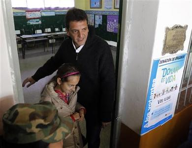 Sergio Massa, major of Buenos Aires' Tigre town, leaves after voting for primary elections, with his daughter Milagros at a polling station in a public school in Tigre August 11, 2013. REUTERS-Enrique Marcarian
