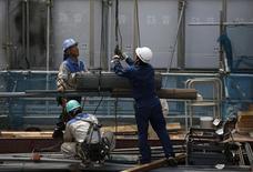 Trabajadores cargan planchas de acero en una obra en construcción en Tokio. Agosto 12, 2013. REUTERS/Issei Kato. La economía de Japón creció a un ritmo más lento que el previsto en el segundo trimestre, lo que ofrece argumentos para quienes buscan retrasar un alza programada del impuesto sobre las ventas incluso cuando la deuda pública ha aumentado más allá de 1.000 billones de yenes (10,4 billones de dólares).