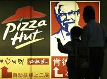 People stand in front of a poster of KFC and Pizza Hut in Guangzhou, capital of south China's Guangdong province April 2, 2007. REUTERS/Joe Tan