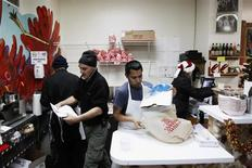 """Small-business owners Ralph Gorham (2nd L) and Susan Povich (R) work with their employees to sell lobster rolls at their shop """"Redhook Lobster Pound"""" in New York December 16, 2010. REUTERS/Lucas Jackson"""