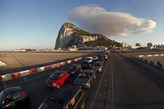 Очередь из автомобилей на дороге из аэропорта Гибралтара в Испанию 9 августа 2013 года. Британия пригрозила во вторник пойти на беспрецедентный шаг в отношении партнера по Европейскому союзу и обратиться в суд, чтобы заставить Мадрид отказаться от усиления проверок на границе с Гибралтаром - заморской британской территорией, которая некогда принадлежала Испании. REUTERS/Jon Nazca