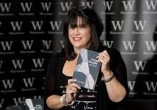 """La escritora E.L. James posa con un ejemplar de la primera parte de su trilogía """"Shades of Grey"""" durante un evento de firmas de libros en Londres. Foto de archivo. REUTERS/Neil Hall. La británica E.L. James, autora de la serie de novelas eróticas """"Fifty Shades of Grey"""", ocupó el primer lugar de la lista de Forbes de los escritores con más ingresos."""