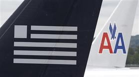 A US Airways plane and an American Airlines plane share a terminal at Ronald Reagan National Airport in Washington April 23, 2012. REUTERS/Kevin Lamarque
