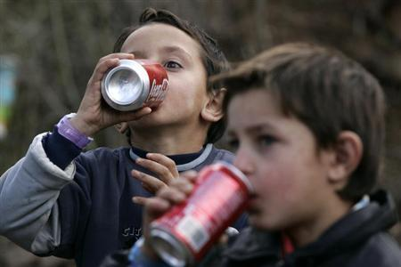Children of the Kosovo Ashkalli minority drink during a ribbon-cutting ceremony for their new home in the village of Magure in central Kosovo October 30, 2007. REUTERS/Hazir Reka