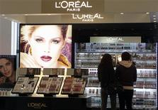 People look at L'Oreal cosmetics in a shop in Riga April 13, 2012. REUTERS/Ints Kalnins