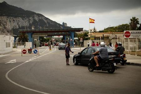 A man begs for money as motorists proceed to enter the British territory of Gibraltar at its border with Spain in La Linea de la Concepcion, southern Spain August 14, 2013. REUTERS/Jon Nazca
