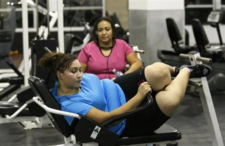 Jazmine Raygoza, 17, (L) does ab crunches during a workout at a gym as her mother Veronica (R) watches in Englewood, Colorado, in this August 24, 2011 file photo. REUTERS/Rick Wilking