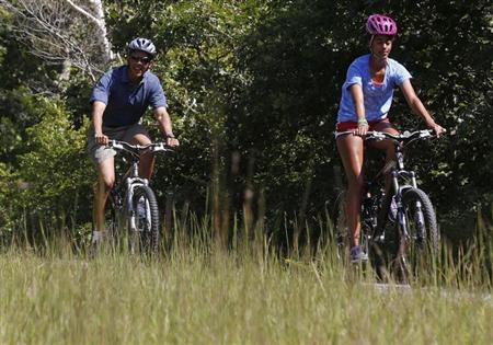 U.S. President Barack Obama (L) bike rides with his oldest daughter, Malia, while at the Manuel F. Correllus State Forest in West Tisbury on their vacation in Martha's Vineyard, August 16, 2013. REUTERS/Larry Downing