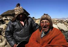 Aymara Indian Carmelo Flores (R) and his son Cecilio joke during a Reuters TV interview in his hometown of Frasquia, 110km (68 miles) north of La Paz, August 16, 2013. REUTERS/David Mercado