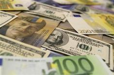 Банкноты доллара США, евро и швейцарского франка в банковском отделении в Будапеште 8 августа 2011 года. Доллар поднялся к корзине валют в понедельник в преддверии публикации протокола июльского заседания ФРС США на этой неделе. REUTERS/Bernadett Szabo