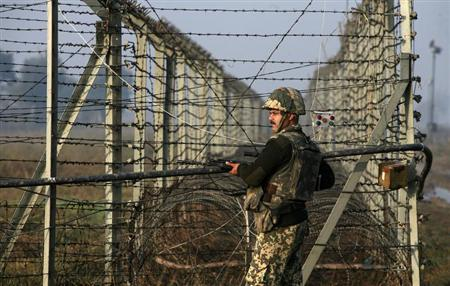 An Indian Border Security Force (BSF) soldier patrols near the fenced border with Pakistan in Suchetgarh, southwest of Jammu January 11, 2013. REUTERS/Mukesh Gupta