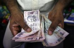A private money trader counts Indian Rupee currency notes at a shop in Mumbai August 1, 2013. REUTERS/Vivek Prakash