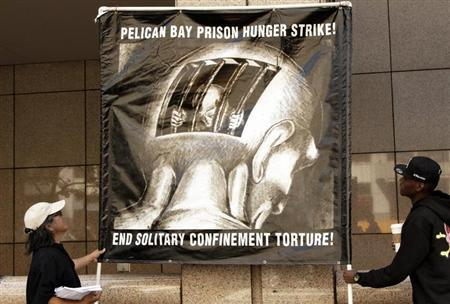 Men hold up a sign during a rally supporting hunger strikers in the California prison system in Los Angeles, California July 29, 2013. REUTERS/Jonathan Alcorn