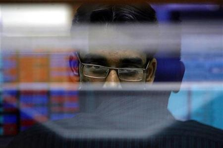 A broker looks at a terminal while trading at a stock brokerage firm in Mumbai October 6, 2008. REUTERS/Arko Datta/Files