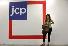 A woman checks her phone outside the entrance of a J.C. Penney store in New York in this file photo taken August 14, 2013. REUTERS/Brendan McDermid/Files
