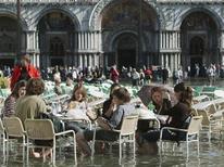 Turistas comem na praça São Marcos alagada, em Veneza. Todo mundo sabe que a cidade alagada pode ser cara, mas sete turistas de Roma tiveram uma amarga surpresa quando sua conta por quatro cafés e três licores em um café ao ar livre superou os 100 euros (130 dólares). 24/10/2006. REUTERS/Manuel Silvestri
