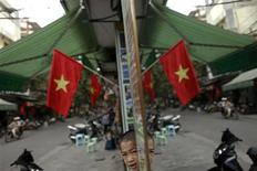 A Vietnamese boy is reflected in a mirror along a street decorated with national flags, in downtown Hanoi October 27, 2010. REUTERS/Damir Sagolj