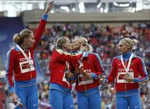 """Duas atletas da equipe russa, medalhistas de ouro no revezamento 4x100 do Mundial de Atletismo, beijam-se durante a cerimônia de entrega de medalhas, em Moscou. Kseniya Ryzhova lamentou que seu beijo em Yulia Gushchina tenha ofuscado a comemoração da vitória russa no revezamento 4x400m no sábado, e negou nesta terça-feira que o """"selinho"""" dado em uma colega no pódio fosse um protesto contra a polêmica lei local que proíbe a apologia à homossexualidade. 17/08/2013. REUTERS/Grigory Dukor"""