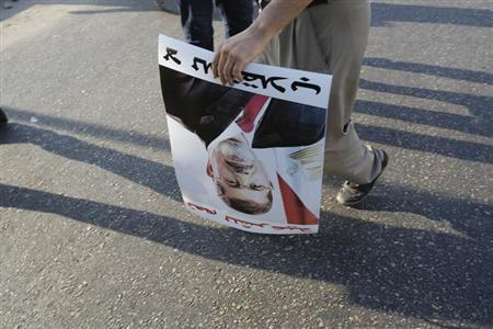 A supporter of deposed Egyptian President Mohamed Mursi holds a poster of him during a protest along Zahara street in Cairo August 18, 2013. REUTERS/Youssef Boudlal