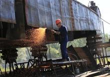 Рабочий разрезает борт старой баржи на ремонтно-эксплуатационной базе в поселке Подтесово 4 июля 2013 года. Экономика России выросла в июле 2013 года на 1,8 процента в годовом выражении, за семь месяцев - расширилась на 1,4 процента, а за весь год рост будет ниже 2,4 процента, сказал на брифинге во вторник замминистра экономики Андрей Клепач. REUTERS/Ilya Naymushin