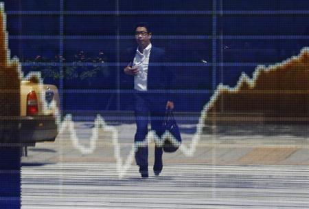 A man is reflected on a stock quotation board displaying a graph of Japan's Nikkei average outside a brokerage in Tokyo August 16, 2013. REUTERS/Toru Hanai