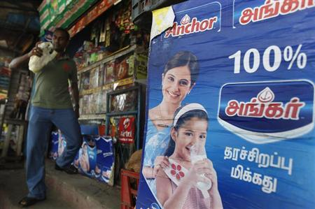 An advertisement for Fonterra's Anchor powder brand is seen at a shop as a customer walks by in Colombo August 15, 2013, a day before the announcement on the ban of advertising for Fonterra milk products. REUTERS/Dinuka Liyanawatte